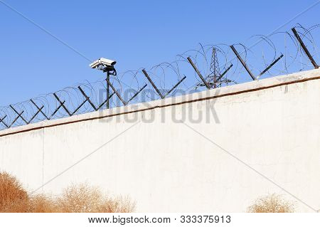 Security Camera Behind Barbed Wire Fence Stretched Around Prison Walls. Security, Surveillance Camer