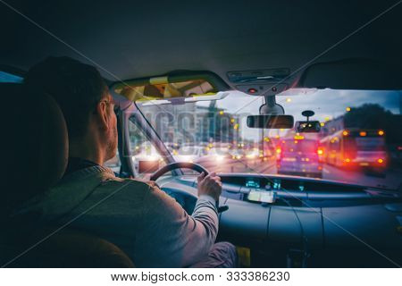 Driving a car in the city at night in traffic jams. A concept of a difficult return home
