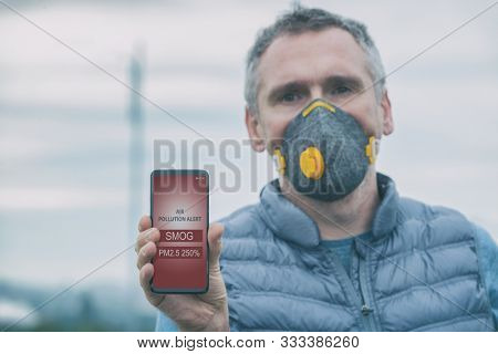 Man wearing a real anti-pollution, anti-smog and viruses face mask and checking current air pollution with smart phone app