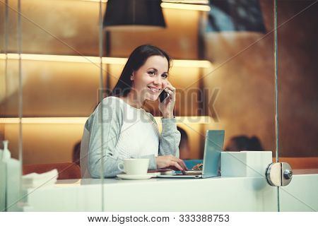 Beautiful Caucasian Woman Uses Phone While Sitting With Portable Net-book In Modern Cafe Bar, Young
