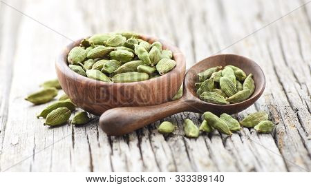 Green cardamom pods on wooden board