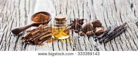 A bottle of essential oil with spices on wooden background. Cinnamon,vanilla, nutmeg and anise.