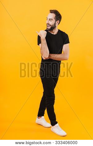 Full length image of unshaved man in basic clothes smiling and pointing finger aside isolated over yellow background