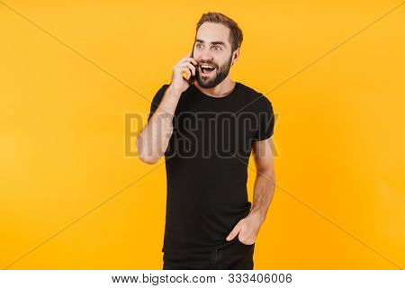 Image of unshaved man wearing basic black t-shirt rejoicing and talking on smartphone isolated over yellow background