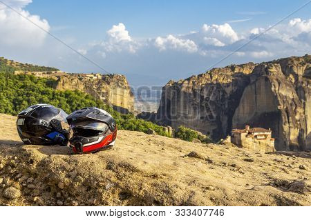 Meteora, Greece - July 23, 2018: Two Motorcycle Helmets Against The Blurred Meteora Valley With The