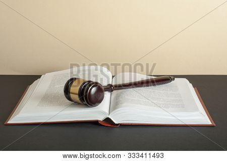 Law Concept - Wooden Judge Gavel On Open Book On Table In A Courtroom .