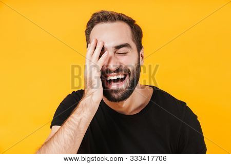 Image of unshaved man in basic black t-shirt laughing and touching his face isolated over yellow background