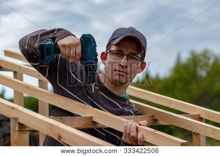 Installation Of The Roof Of The Rural Toilet. A Male Builder Screws The Wooden Beams Of The Rafters
