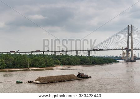 Ho Chi Minh City, Vietnam - March 12, 2019: Song Sai Gon River. Short Tugboat Pushes Long Barge With