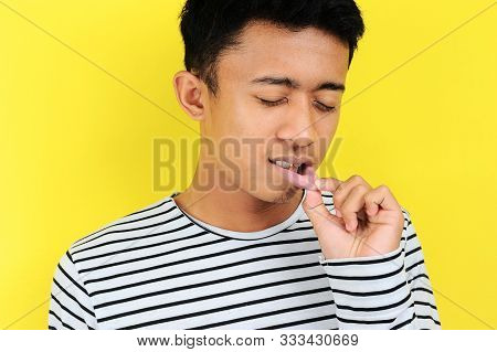 Young Asian Man Showing Ulcer Or Blister In His Mouth At Camera, Isolated On Yellow Background