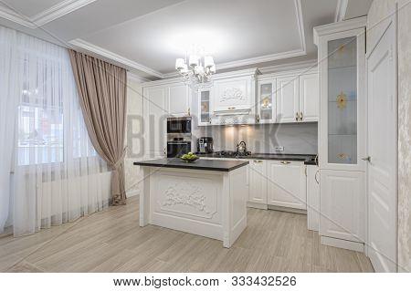 White luxury spacious modern kitchen with island interior