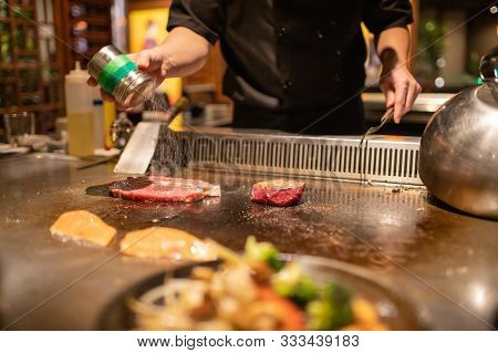 Teppanyaki Chef Cooking Japanese Wagyu Beef And Filet Mignon Steak On Hot Metal Plate
