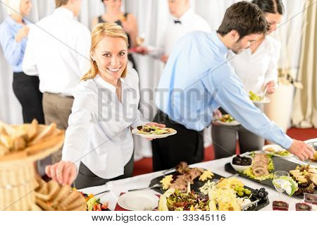 Business woman serve herself at buffet catering service company event