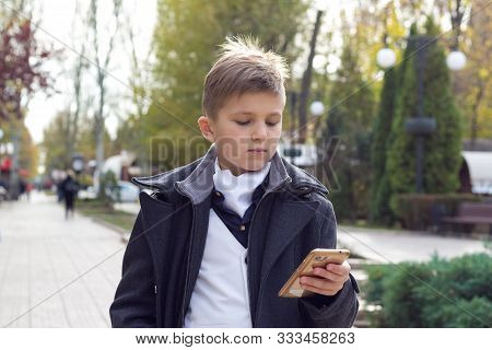 Schoolboy Dressed In Stylish Business Clothes Holding Smartphone In Hand And Watching On Touch Scree