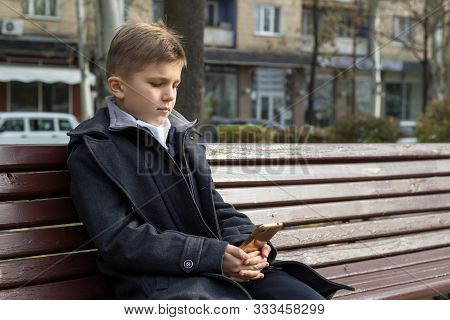 A School-aged Boy Sits On A Bench In A Park In A Beautiful Business Coat And Looks At Something On H