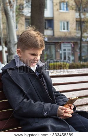 A Boy With An Irritated Expression In A Business Suit Sits On A Bench With A Smartphone.he Does Not