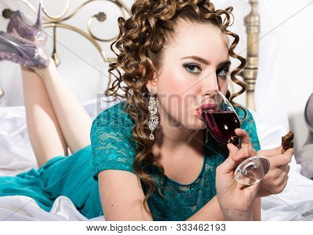 Young Happy Cheerful Curly Woman With Glass Of Red Wine And Chocolate. Lady Resting On The Bed