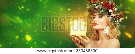 Christmas winter beauty woman. Charming blonde girl with Christmas decoration on her head holds a gift box and smiles. Studio portrait over green background. Copy space.