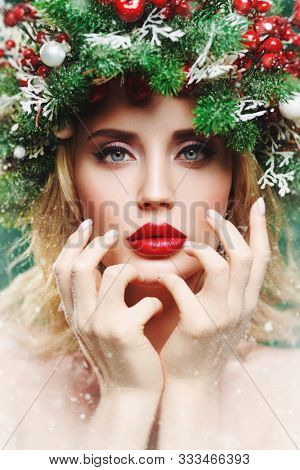 Close-up portrait of a beautiful Christmas woman with a Christmas spruce wreath on her head, decorated with Christmas balls, berries and snowflakes. Winter beauty girl. X-mas makeup and cosmetics.