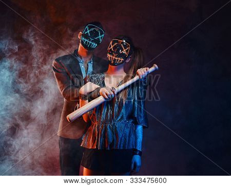 In Misty Smoke Strange Couple In Creepy Masks Are Posing For Photographer With Baseball Bat.