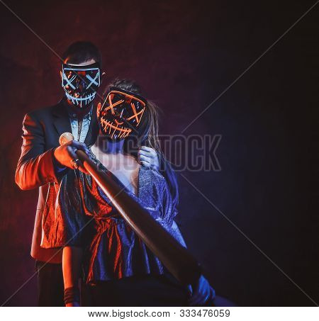 Crazy Couple In Spooky Masks Are Posing For Photographer With Baseball Bat.