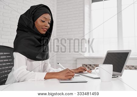 Side View Of Attactive Muslim Woman Wearing Black Hijab Using Computer And Working In Office. Smart