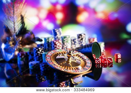 Casino. Gambling Games Theme.  Roulette Wheel, Dice And Poker Chips On Color Bokeh Background.