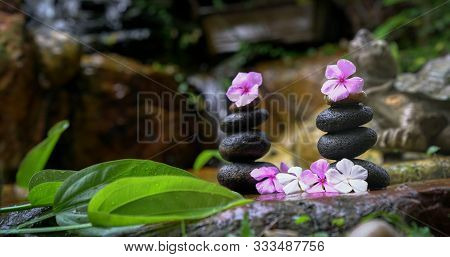 Stack Of Zen Stones With Flowers Next To A Garden Mini Waterfall. Zen Or Spa Or Wellness Concept.
