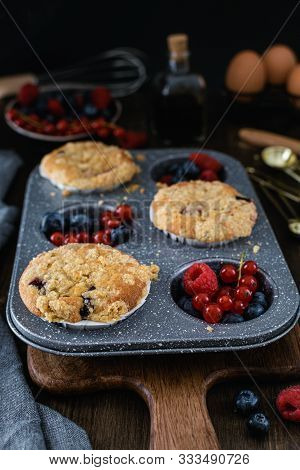 Streusel Muffins With Blueberry, Raspberry And Red Currant On Rustic Wooden Table