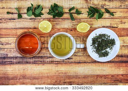 Foodstuffs For Kept Healthy. From Left - Brown Honey, Salvia Hot Tea, Nettle On Plate. Also Lemons A