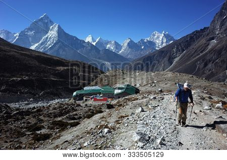 Everest trek, Hiker walking trail up from Dughla (4620 m) with view of Ama Dablam (6856 m) in Himalayas mountains, Sagarmatha national park, Solukhumbu, Nepal