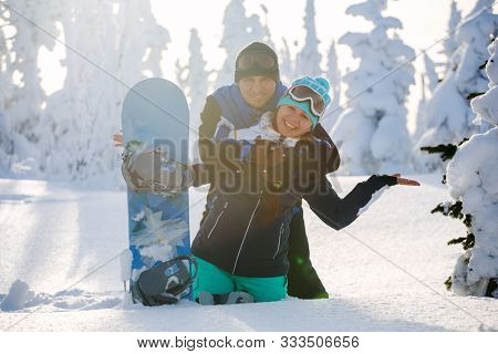 Loving couple of young people with a snowboard in deep snow. Ski resort Sheregesh. Russia.