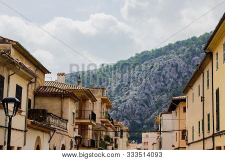 Street View In The City Of Pollenca With Mountains In Background, Mallorca, Spain, 2018. Historical