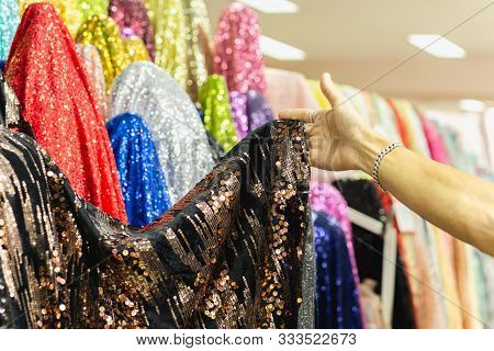 Hand Pick A Roll Of Sequin Fabric Cloth In Fabric Store.