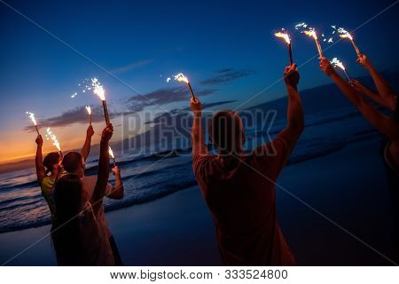Group Of Happy Friends Are Having Fun At Sunset Beach Party With Fireworks