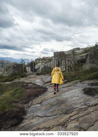 Songesand, Norway, September 9, 2019: Young Girl In Yellow Rain Coat On Hike To Preikestolen Massive