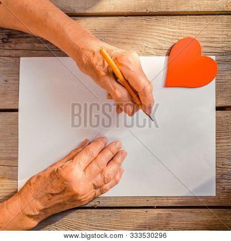 Elderly Woman Hand Going To Write A Letter, Red Heart On Rustic Wooden Table As A Background, Sun Ra