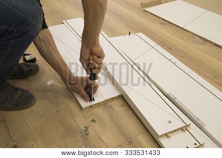 Furniture, Home And Moving Concept - Close Up Of Male Hands Assemblying Home Furniture.