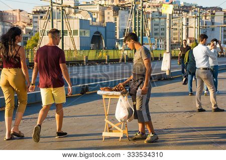 Istanbul, Turkey - September 6th 2019. A Young Food Vendor Sells Sweet Deep Fried Pastries To Passer