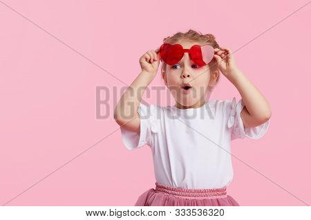 Portrait Of Surprised Cute Little Toddler Girl In The Heart Shape Sunglasses. Child With Open Mouth