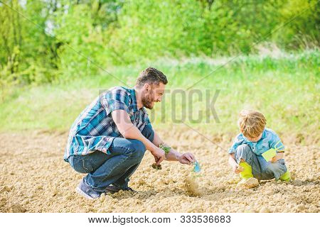 Eco Living. Happy Earth Day. Family Tree. Father And Son Planting Flowers In Ground. New Life. Soils