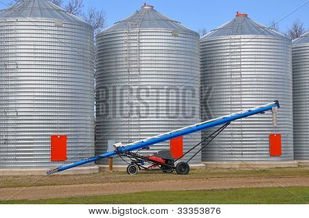 Auger In Front Of Farm Grain Bins