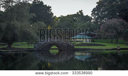 Reflection Of A Stone Bridge In A Park In Hilo