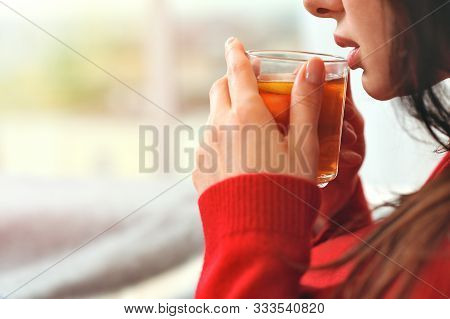 Young Woman Relaxing Holding Cup With Lemon Tea. Girl Dreams Looking Out The Window . Young Female T