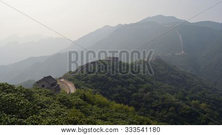 The Great Wall Protecting The Frontier Through The Mountains Surrounded By Dense Forest, Mutianyu Se