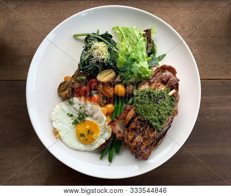 Top View Steak And Egg Entree With Spinach, Potatoes, Lettuce, Green Beans, Cherry Tomatoes In Natur