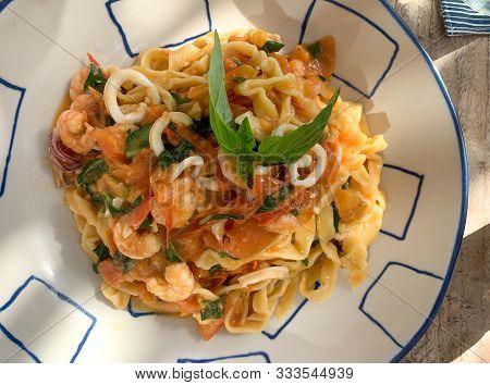 Shrimp, Calamari, Herbs, Handmade  Italian Pasta Linguine Entree. Natural Daylight Tree Shadow Dappl