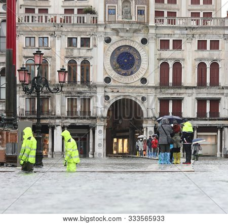 Saint Mark Square In Venice In Italy During The High Tide And The Clock Tower With Statue On Top