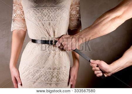 Man Tightly Tightens The Belt At The Woman S Waist, Close Up
