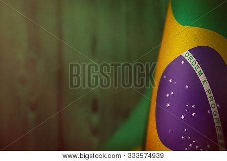 Brazil Hanging Flag For Honour Of Veterans Day Or Memorial Day On Green Blurred Natural Wood Wall Ba